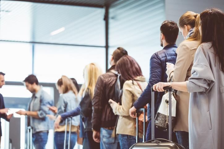 Gruppe von Personen, die am Flugsteig in der Warteschlange stehen.